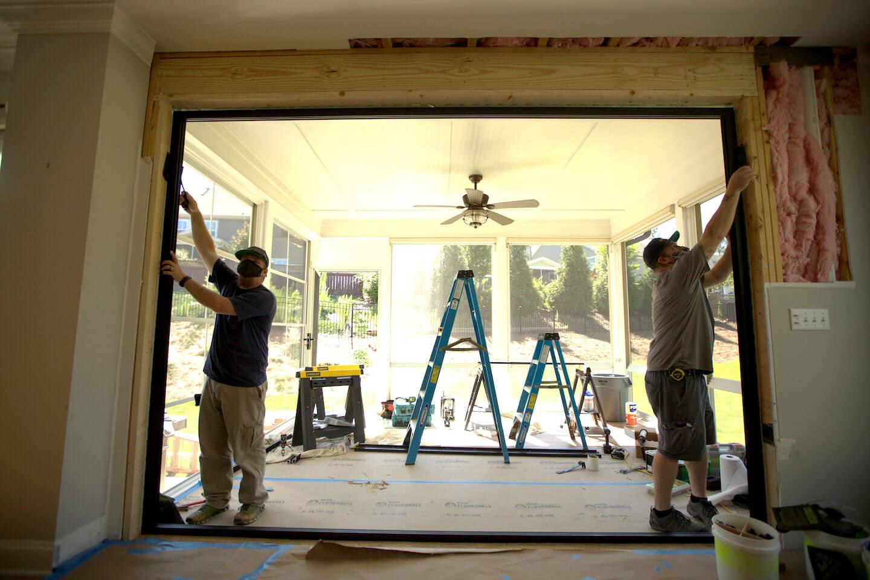 Two men install bifold doors